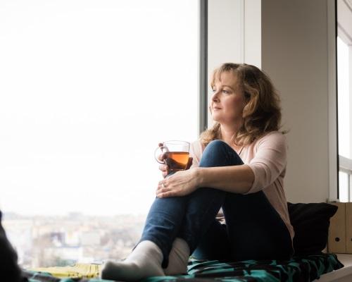 Senior woman drinking tea and looking through window