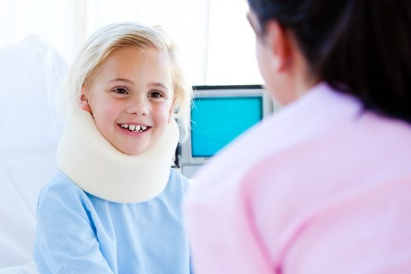 Kleines Mädchen mit einer Nackenstütze im Gespräch mit einer Krankenschwester sitzt auf einem Krankenhausbett