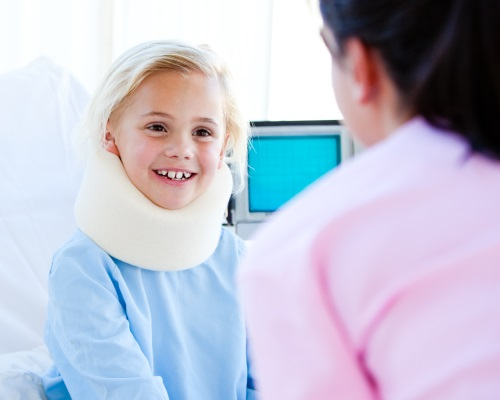 Little girl with a neck brace talking with a nurse