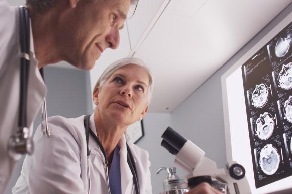 Médicos hablando frente a un microscopio